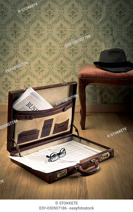 Vintage businessman open briefcase on the floor with financial newspaper and hat