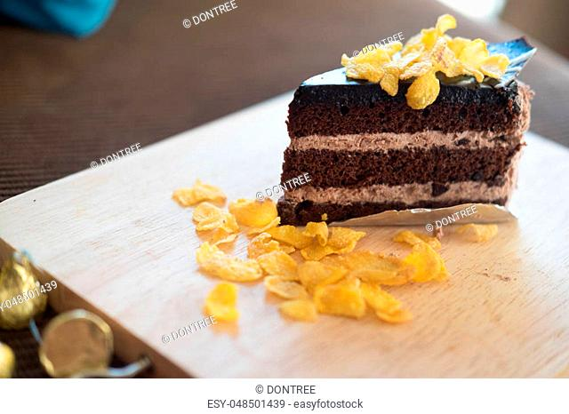 Chocolate cake with corn flakes topping in cafe on wood tray
