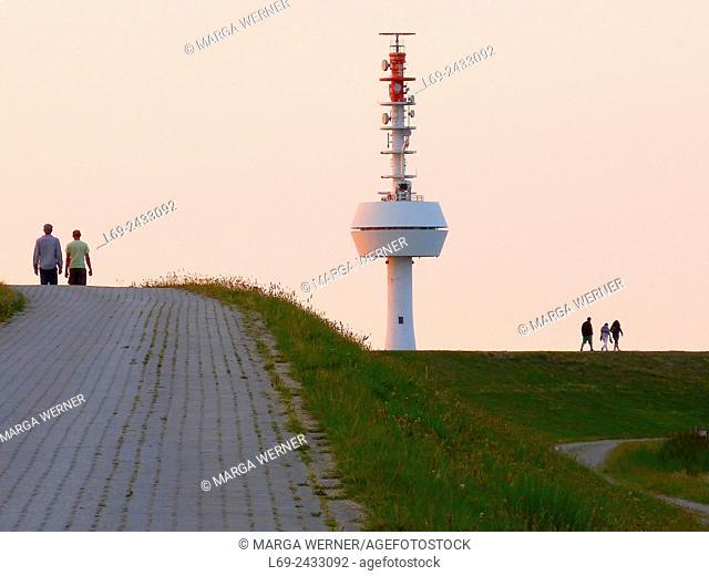 People walking on a dyke on island Neuwerk, Elbe estuary, North Sea, Hamburg, Germany