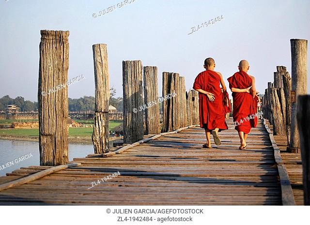 Two young monks crossing U Bein bridge. Myanmar, Mandalay, Amarapura, U Bein