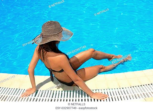 Young woman sitting on the ledge of the pool