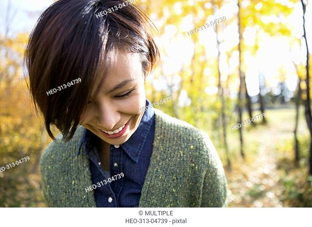 Smiling brunette woman looking down in autumn woods
