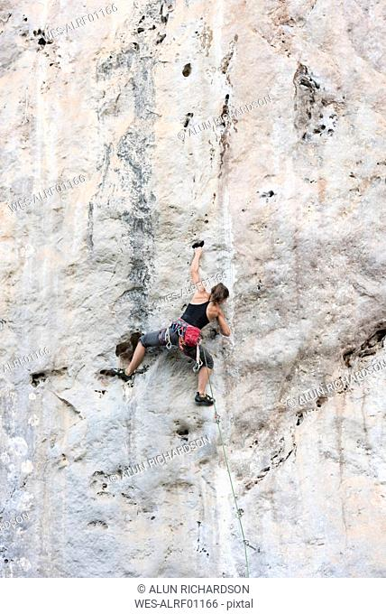Thailand, Krabi, Chong Pli, woman climbing in rock wall