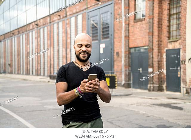 Portrait of smiling man looking at his cell phone