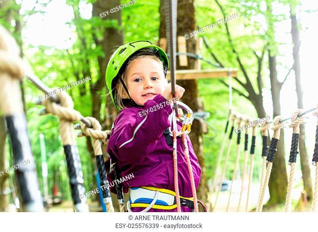 Kind seilt sich an im Hochseilgarten
