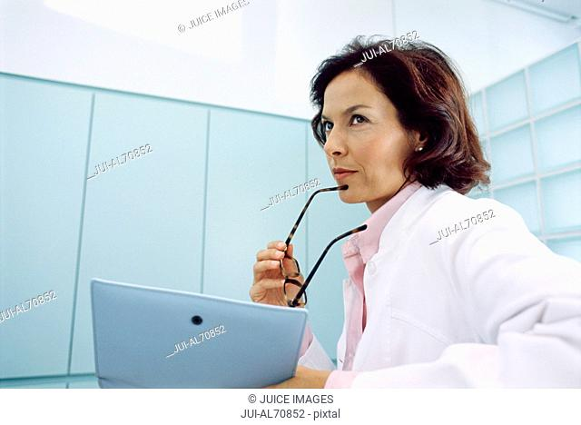 Low angle view of a female doctor looking at a clipboard