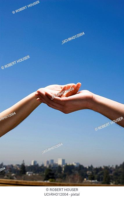 People cupping hands above cityscape