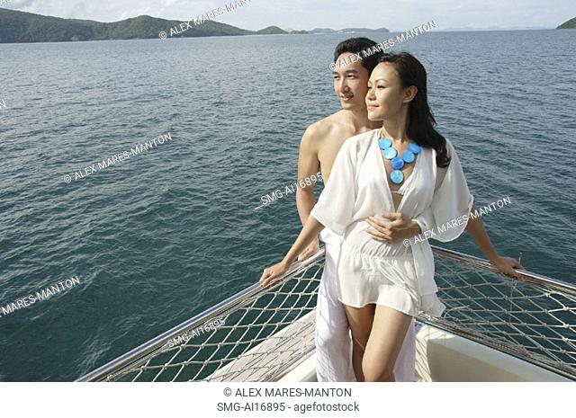 Couple standing on yacht, portrait