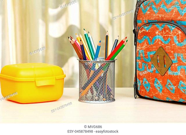 School backpack with school supplies. Metal stand for pencils with color pencils and yellow sandwich box on wooden table. Back to school concept