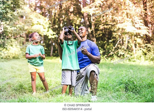 Father with son and daughter bird watching in eco forest camp