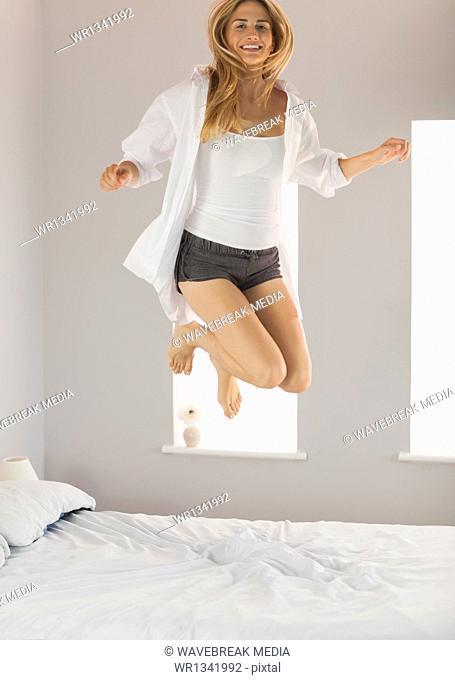 Fun blonde wearing white mens shirt jumping on bed