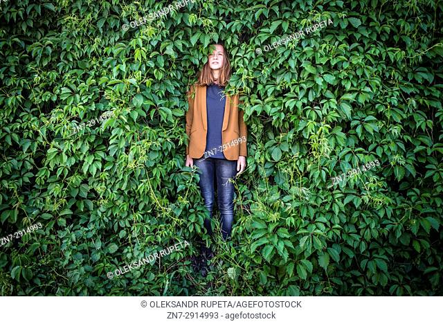 A young woman stands near a wall surrounded by greenery