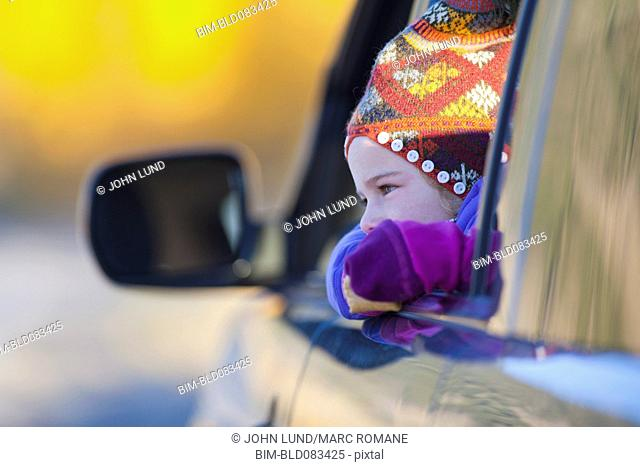 Caucasian girl looking out car window