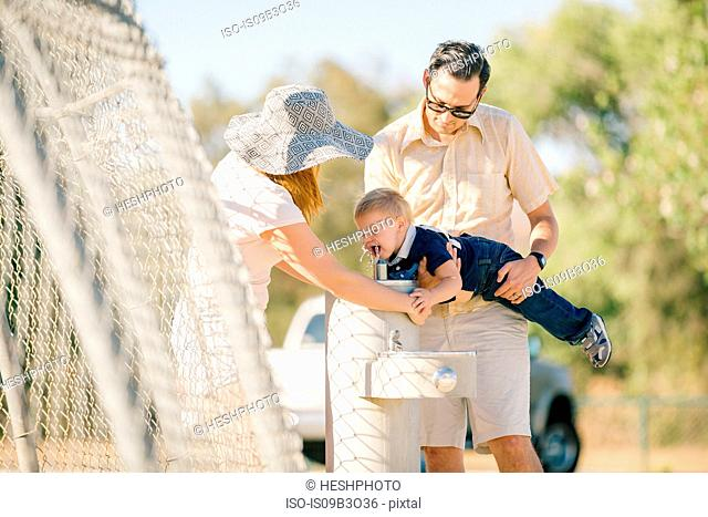 Family at playground, father holding young son over water fountain