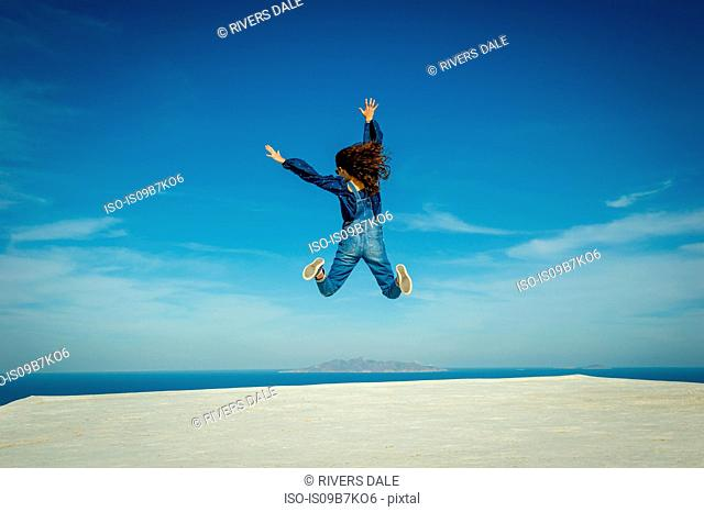 Girl in midair, sea and sky in background, Oía, Santorini, Kikladhes, Greece