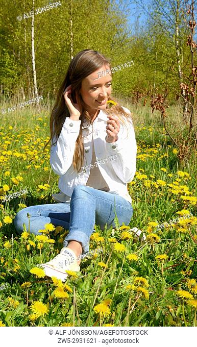 Young beautiful woman sit on a meadow with dandelion in springtime in Scania, Sweden