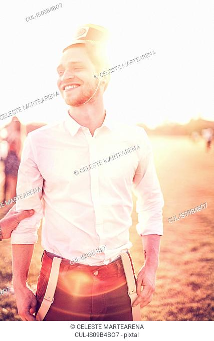 Young man in party hat laughing in sunlit field, Tucuman, Argentina