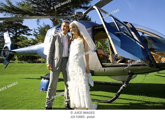 Bride and groom by helicopter, smiling, portrait, low angle view