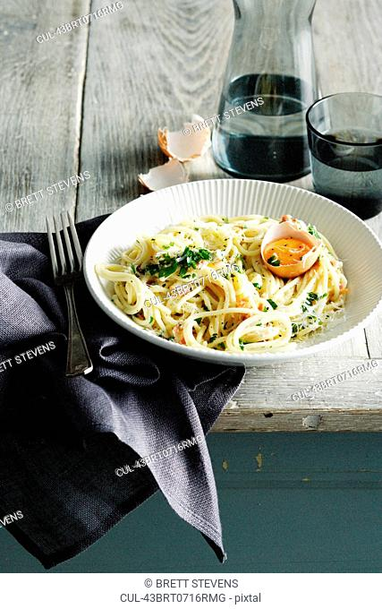 Bowl of pasta carbonara with egg