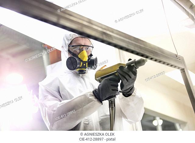 Worker in protective workwear using drill in factory