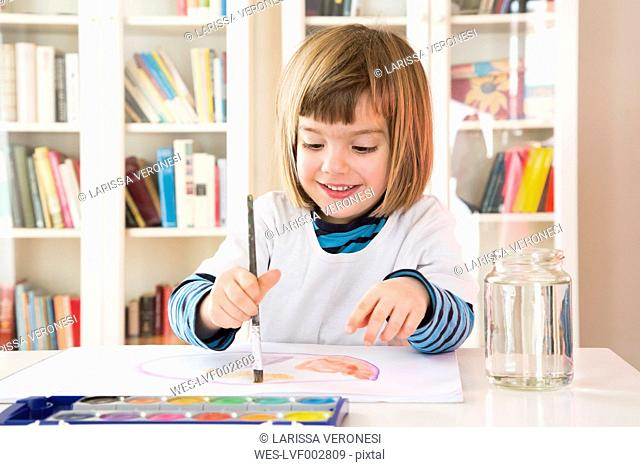 Portrait of smiling little girl painting with watercolours