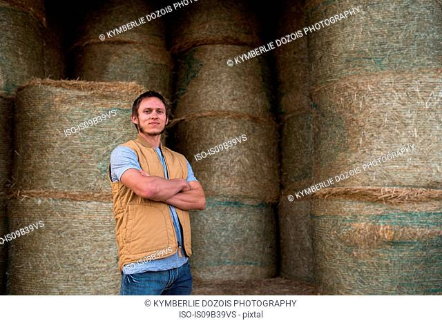 Portrait of farmer, standing in front of hay shed