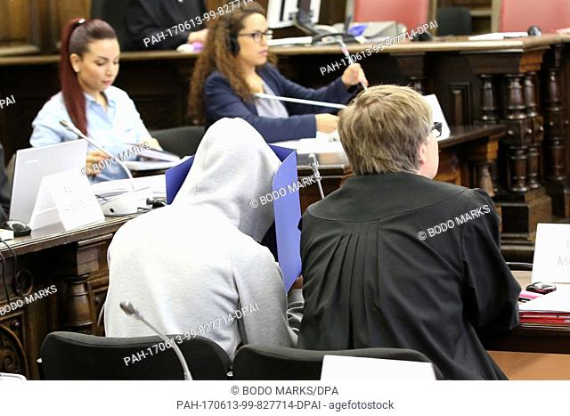 One of the three defendants, Mahir A. (2nd r) and his lawyer Andreas Mross (r) as well as other people involved in the trail sit in the regional court during...
