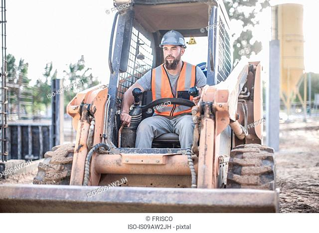 Builder driving excavator on construction site