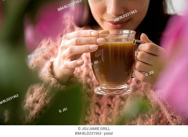 Hispanic woman drinking coffee behind flowers