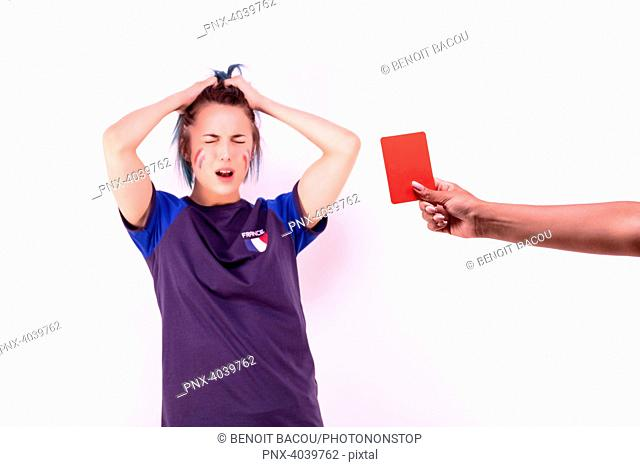 Portrait of a young supporter of the French football team facing a red card