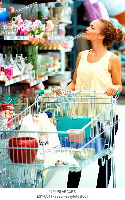 Attractive young ethnic woman standing with trolley looking at higher shelf