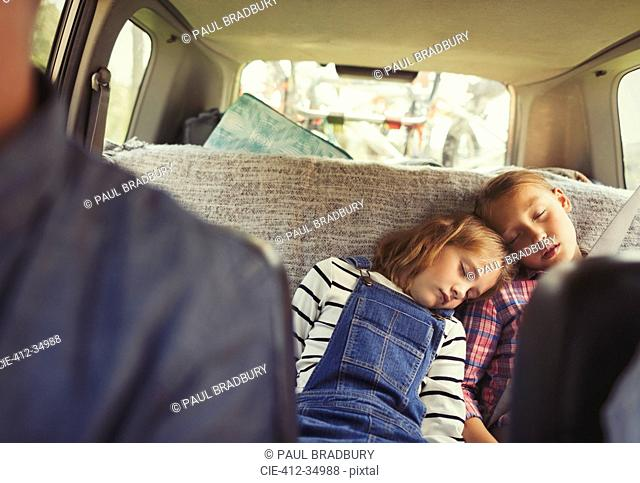 Tired sisters sleeping in back seat of car