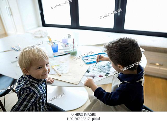 Brothers watercolor painting at table