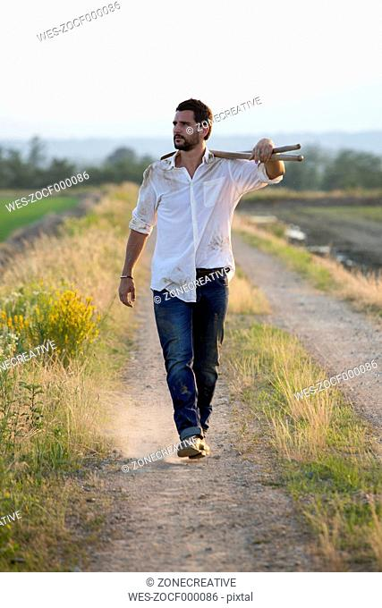 Young man walking on field path