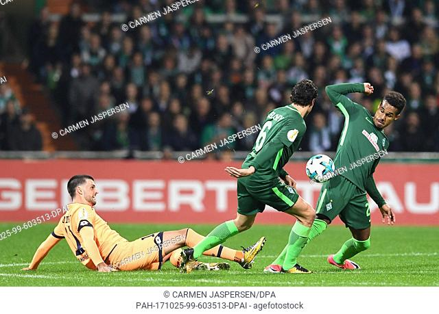 Bremen's Thomas Delaney (C) and Theodor Gebre Selassie (R) vying for the ball against Hoffenheim's Florian Grillitsch during the DFB Cup soccer match between...