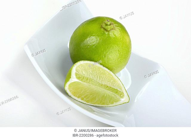 Limes (Citrus latifolia), whole and sliced, in a white bowl