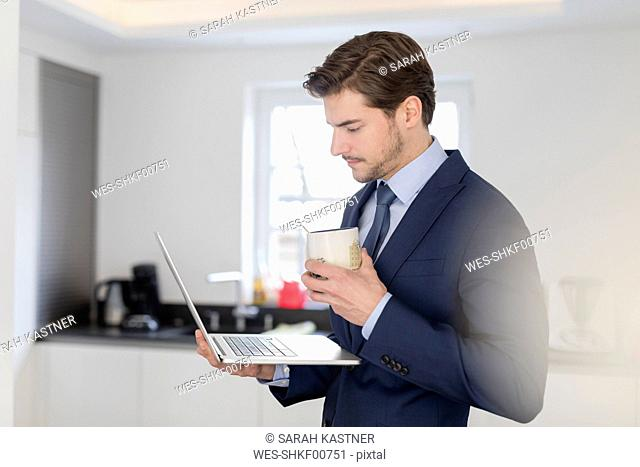 Businessman at home holding laptop and cup of coffee