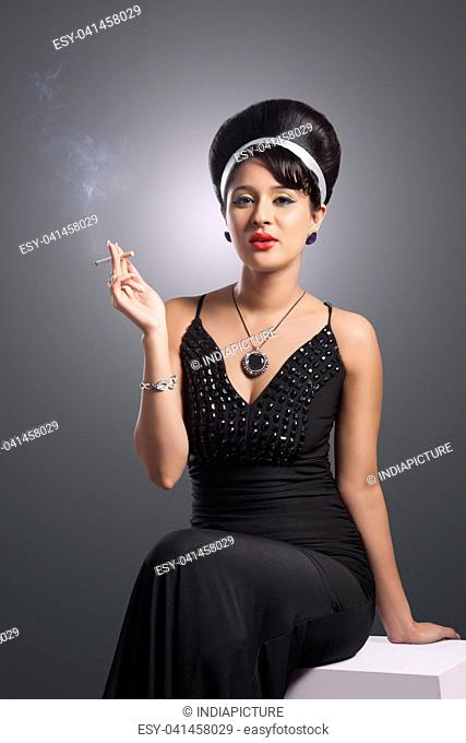 Portrait of young woman in evening gown smoking