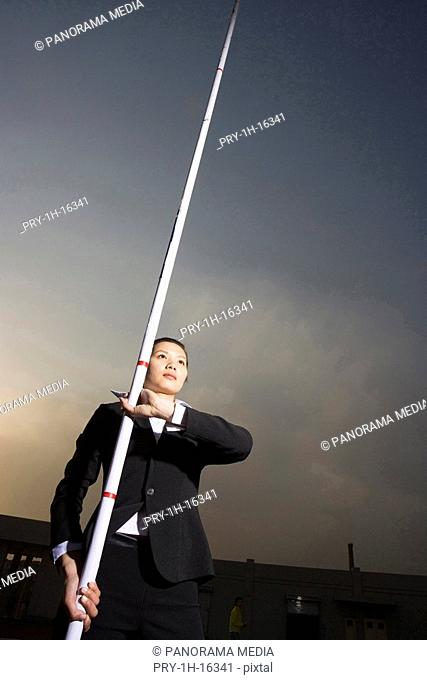 a woman in business suit with a pole in her hand