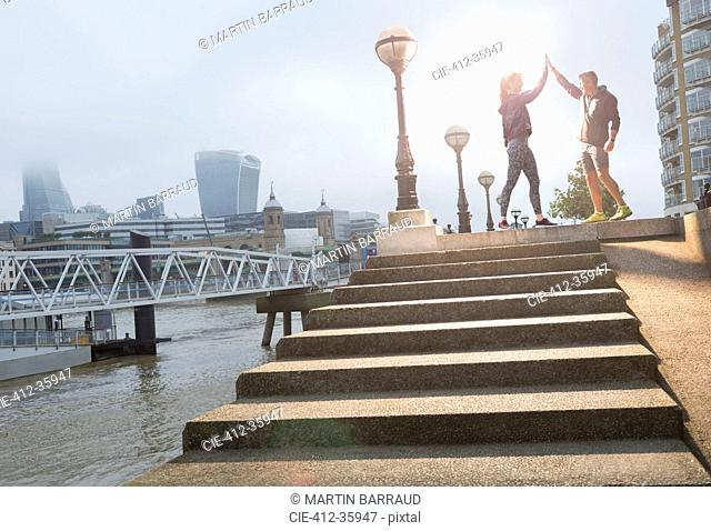 Runners high-fiving on sunny urban steps