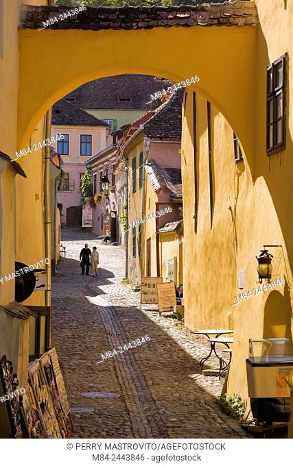 Cobblestone street with souvenir shops and tourists in the medieval town of Sighisoara, Romania, Eastern Europe
