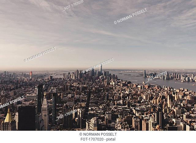 Buildings in Manhattan by river against sky seen from Empire State Building, New York City, USA