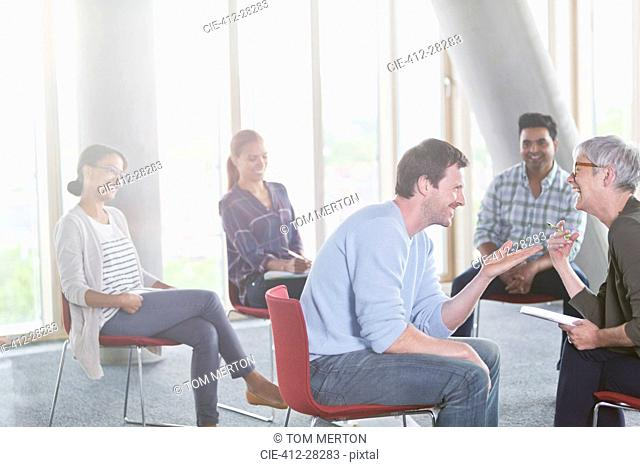 Business people talking and laughing face to face in meeting