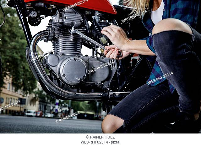 Young woman working on motorcycle