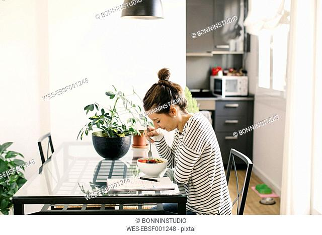 Woman sitting at table with fruit muesli looking at notepad