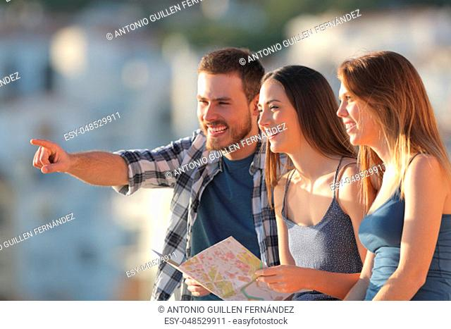 Group of happy tourists contemplating views on vacation at sunset