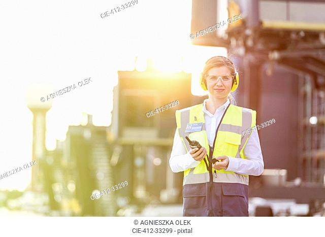 Portrait confident female air traffic controller with walkie-talkie on airport tarmac
