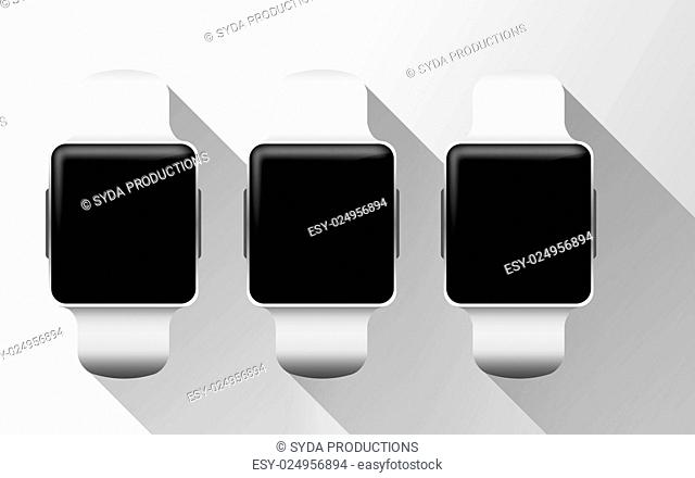 modern technology, object and media concept - close up of smart watches with black blank screen over gray background