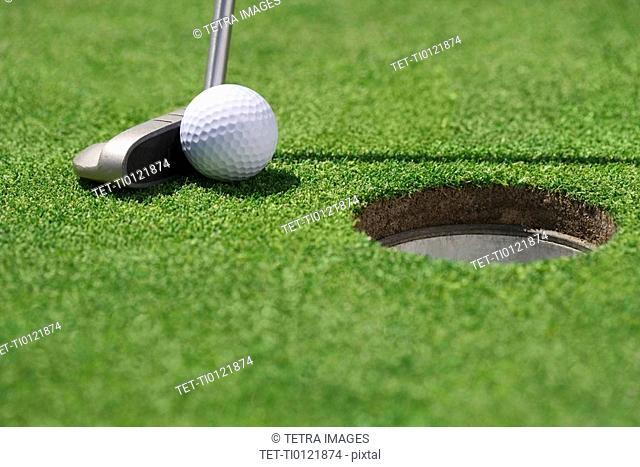 Closeup of golf ball and club near cup