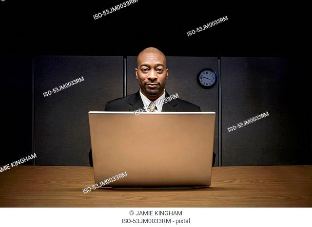 Businessman using laptop in cubicle